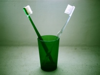 Two toothbrushes in a green cup